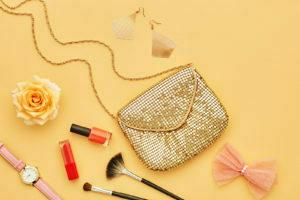 Bolsa e vários cosméticos ao redor.