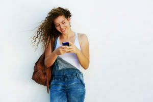 Menina feliz digitando no celular.